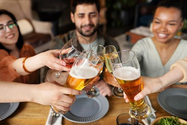 Крупным планом друзья звенящие бокалы
