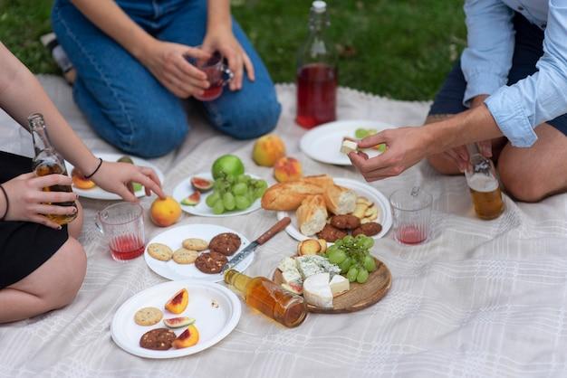ピクニックで食べるクローズアップの友人