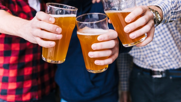 Primo piano della mano degli amici tintinnio dei bicchieri da birra
