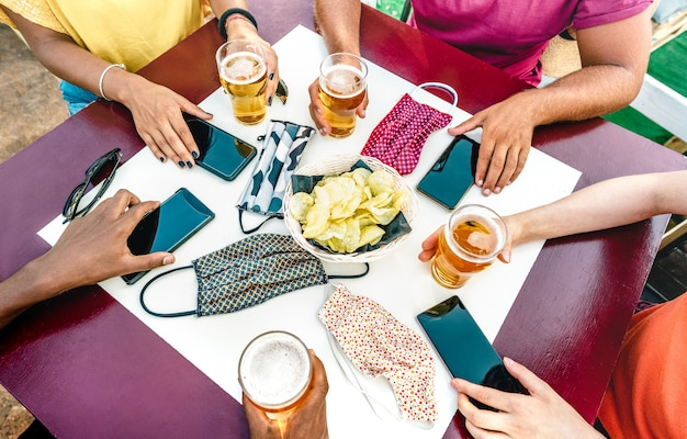 Close up of friends hands near face masks on table with mobile smart phones and beers