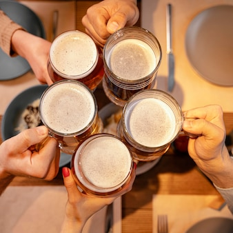 Close-up friends holding beer mugs in pub