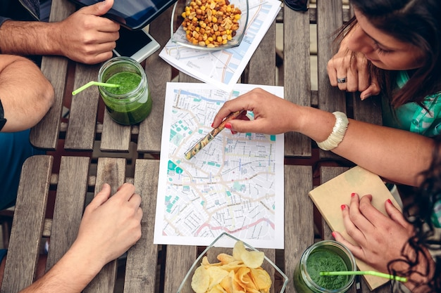 Close up of friends looking map over a wooden table with healthy drinks and snacks. holidays and tourism concept. view from above.