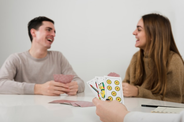 Close-up friends playing cards game