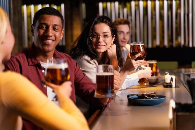 Amici del primo piano che si siedono con la birra