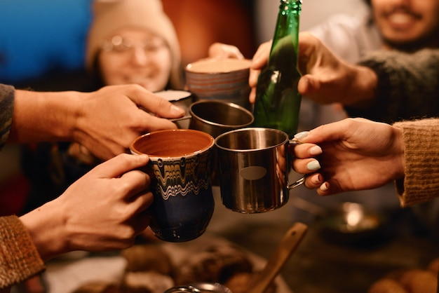 Close-up of friends toasting with cups of drinks during party outdoors