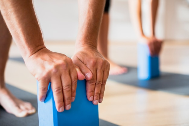 Close-up friends training with pilates blocks