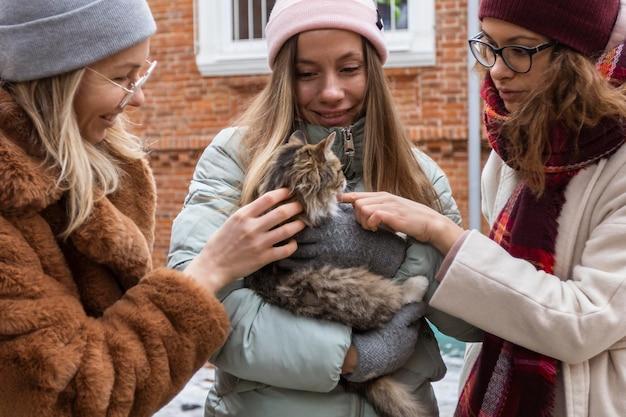 Крупным планом друзья с милой кошкой