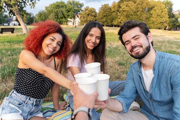 屋外で飲み物を飲みながら友達をクローズアップ