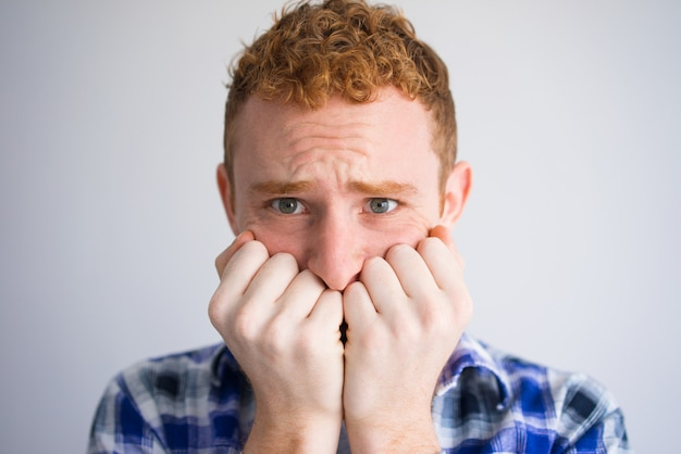 Close-up of frightened male student biting nails