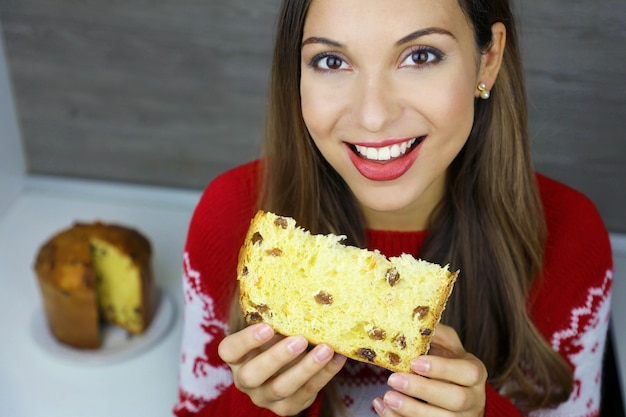 パネトーネのスライスを食べる笑顔の若い女性の上からクローズアップ