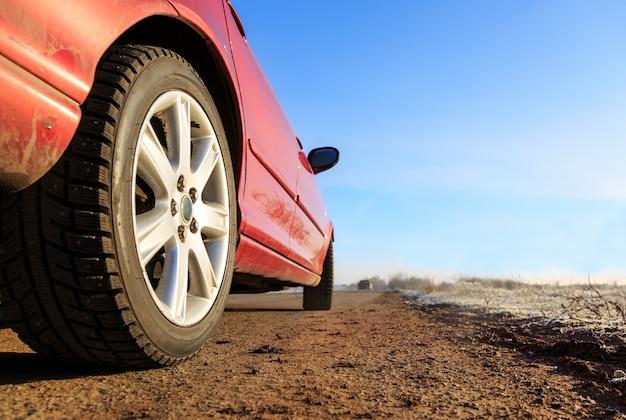 晴れた日にアスファルトの道路に新しい赤い車の前を閉じる
