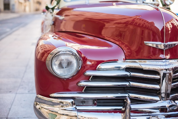 Close-up of a front part and headlight of a red retro car.