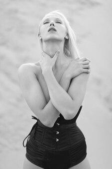 Крупным планом передний портрет молодой женщины со светлыми волосами в черном боди, позирующей в песчаной карьере. черно-белое изображение.