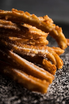 Close-up front view fried churros and sugar
