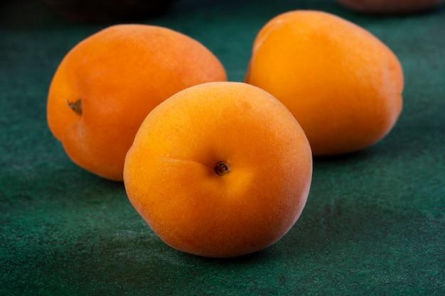 Персики крупным планом вид спереди на зеленый