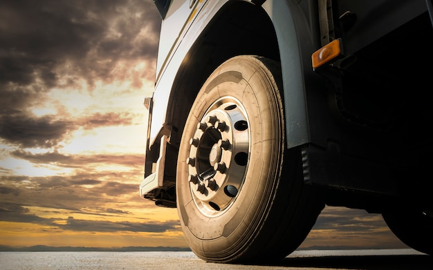 일몰 하늘 산업 화물 트럭 운송에서 세미 트럭 주차의 앞 바퀴를 닫습니다