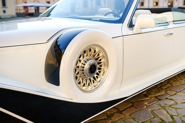 Close-up of the front of a white vintage car in the courtyard of the castle