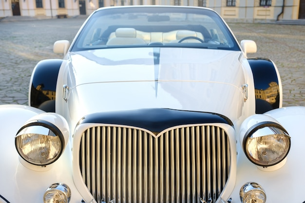 Close-up of the front of a white vintage car in the courtyard of the castle.