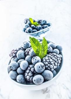 ミントの葉と冷凍ブルーベリーとブラックベリーのクローズアップ。