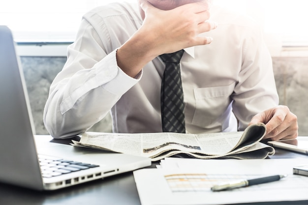 Close up of frustrated businessman reading newspaper on the desk.