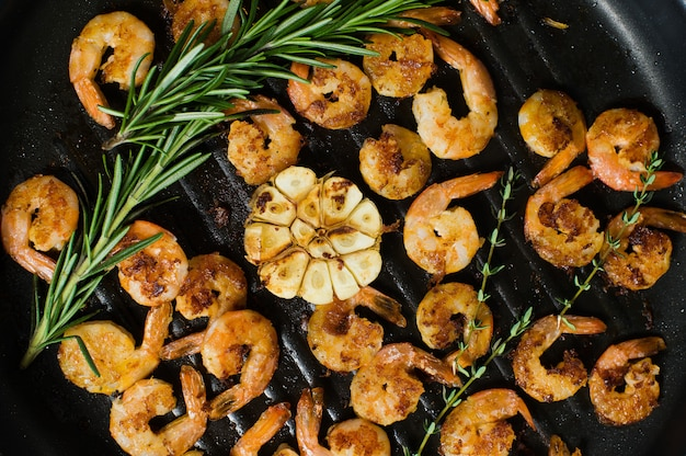Close-up of a frying pan with fried king prawns and sprigs of rosemary and thyme.