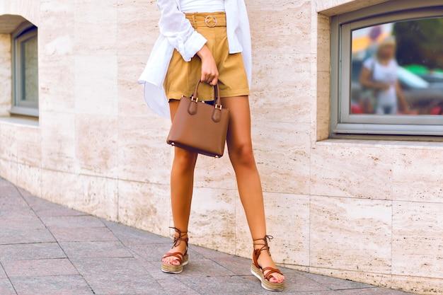 Chiudere i dettagli di moda a tutta lunghezza di gambe lunghe sottili di donna abbronzata, camminando per strada indossando pantaloncini beige di lino, borsa di lusso in pelle caramello, camicia bianca e sandali alla moda gladiatore.