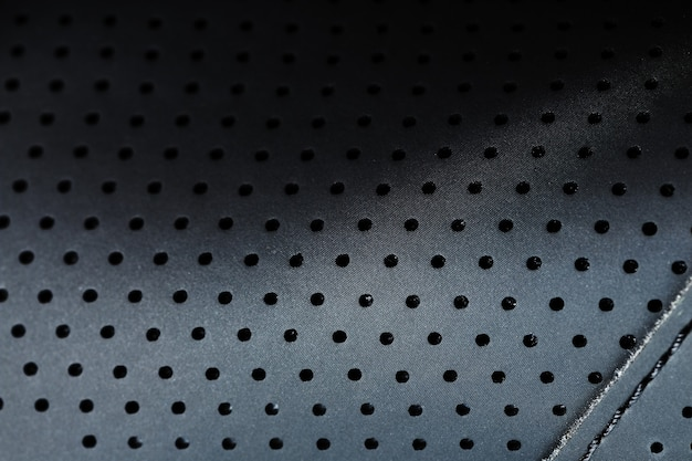 Close-up full-screen black textured leather with perforations
