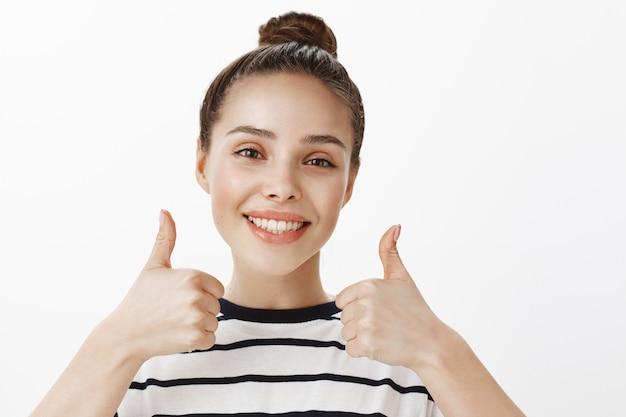 Primo piano della ragazza attraente felice completamente soddisfatta, sorridente sognante, che mostra i pollici in su, approva e raccomanda