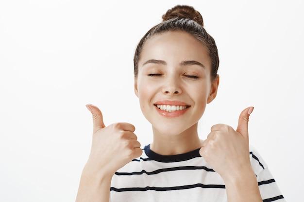 Primo piano della ragazza attraente felice completamente soddisfatta, sorridente con gli occhi chiusi e l'espressione sognante, che mostra i pollici in su, approva e raccomanda