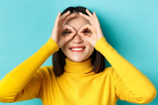 Close up of funny asian girl looking through hand glasses and smiling, checking out promo offer, standing over blue background.