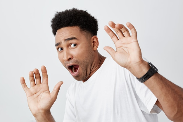 Close up of funny attractive dark-skinned african male student with curly hair in casual white t-shirt spreading hands with frightened expression, watching scary movie in cinema.