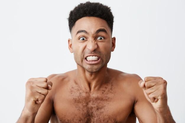 Primo piano di divertente maschio africano dalla pelle scura attraente con i capelli ricci, guardando la tv con espressione folle, tifo per la sua squadra di baseball preferita, urlando e gesticolando con le mani.
