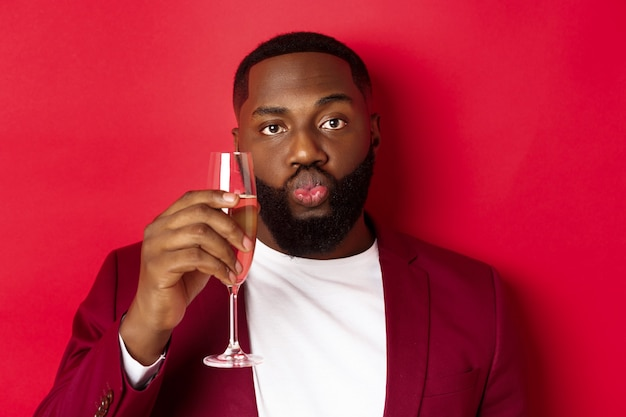 Close-up of funny black man tasting champagne from glass, looking silly and pucker lips