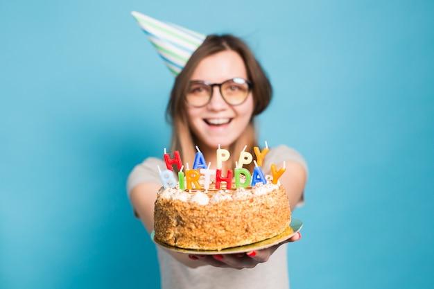 お誕生日おめでとうケーキを保持しているメガネと挨拶の紙の帽子で面白いぼやけたポジティブな女の子をクローズアップ