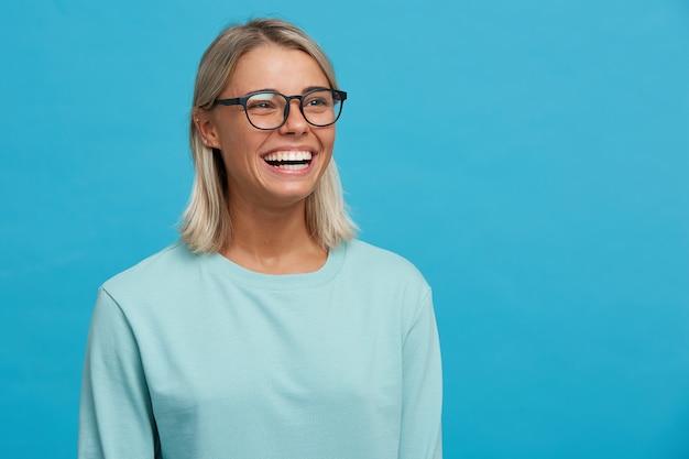 Chiuda in su della giovane donna bionda felice allegra divertente in vetri con il sorriso a trentadue denti