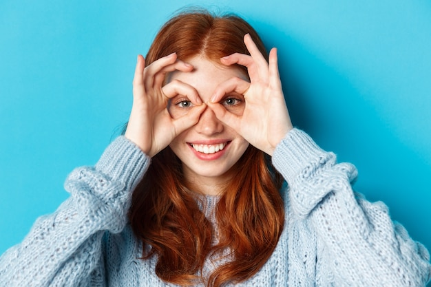 Close-up of funny and cute redhead girl making hand glasses and looking through them, seeing promo offer and smiling, standing over blue background.