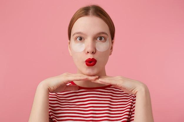 Chiuda in su della giovane signora dai capelli rossi felice carina divertente in una maglietta a strisce rossa, con le labbra rosse, appoggiando il mento sulle mani e molto soddisfatta delle nuove toppe. stand.