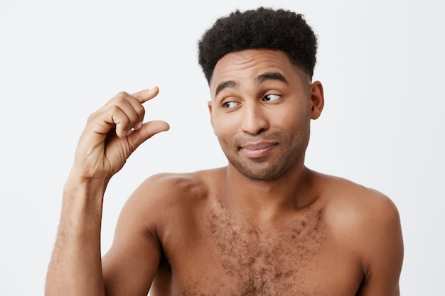 Close up of funny dark-skinned male with afro hairstyle and naked body showing little sign with hand, looking aside with sarcastic expression. people's emotions.