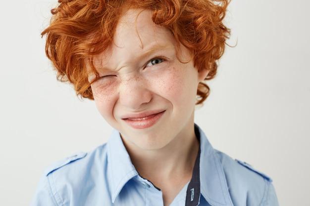 Chiuda in su del ragazzo divertente dello zenzero con le lentiggini e le guance rosse sbaglia l'occhio
