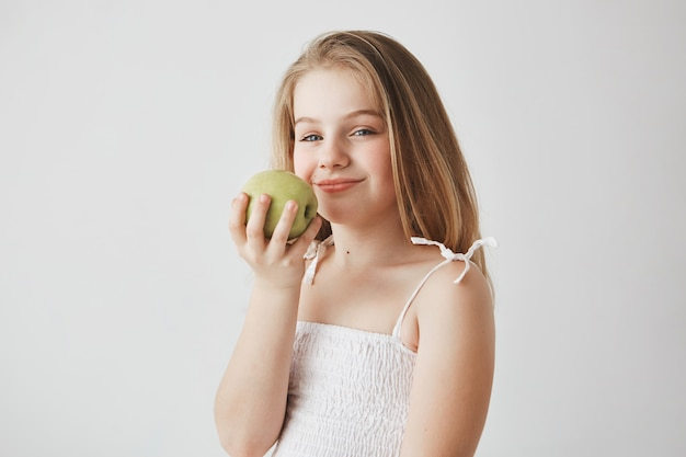 Close up of funny girl with long blond hair holding apple in hands with satisfied expression, going to hava healthy lunch in school.