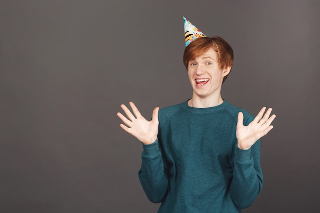 Close up of funny good-looking joyful young ginger guy in green sweater and party cap spreading hands