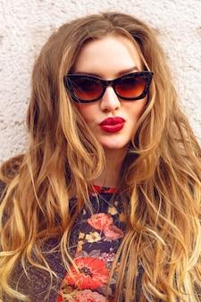 복고풍 스타일의 고양이 눈 선글라스와 밝은 입술을 입고 화려한 금발 생강 긴 곱슬 헤어 스타일을 가진 젊은 여자의 재미있는 장난 초상화를 닫습니다. 패션 소녀 키스 만들기.