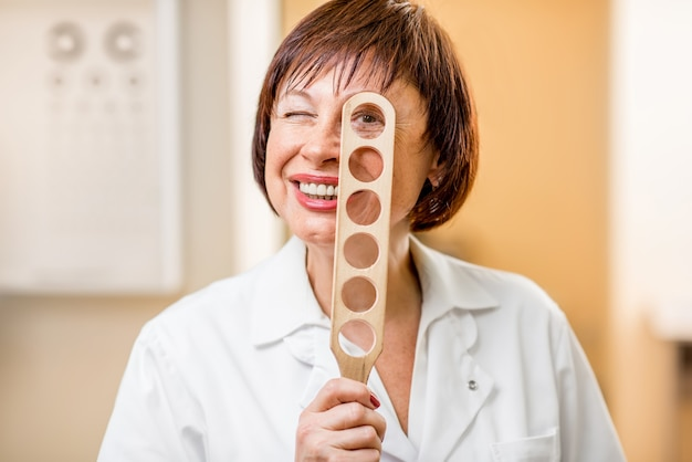 オフィスで視力検査のためのレンズを持って立っている年配の女性眼科医のクローズアップ面白い肖像画