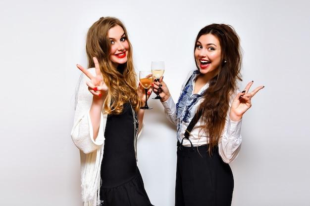 Chiuda sul ritratto divertente di belle ragazze che si divertono su una festa incredibile, trucco luminoso, capelli lunghi, bicchieri con champagne, bel ritratto di migliori amici, immagine con flash.