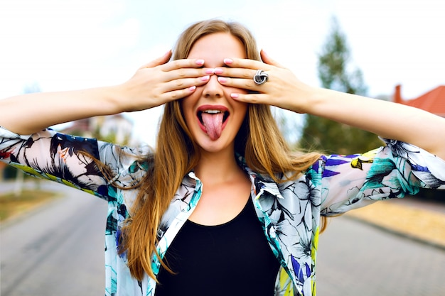 Close up funny portrait of smiling blonde girl close her eyes buy her hands, bright shirt, countryside, shoeing her long tongue, bright manicure.