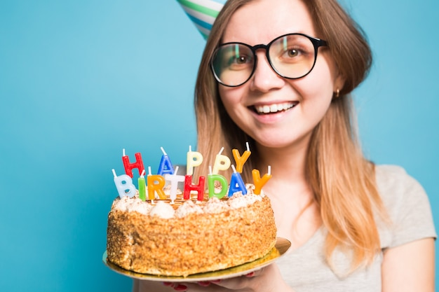 Close up funny positive girl in glasses and greeting paper hat holding a happy birthday cake in her