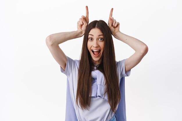 Primo piano di una ragazza divertente e positiva, che fa corna da diavolo di tori con le dita sulla testa, sorride eccitata, in piedi contro il muro bianco