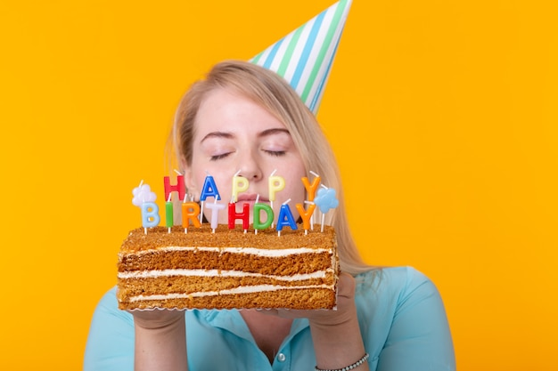 Close-up of funny positive young woman holds in her hands a homemade cake with the inscription happy birthday posing on a yellow wall. concept of holidays and anniversaries.
