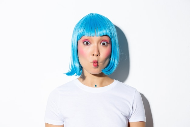 Close-up of funny and silly asian girl entertainer celebrating halloween, wearing blue wig, showing grimaces.