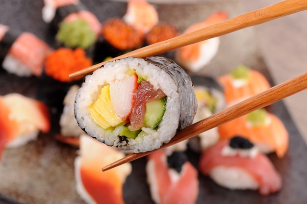 Close-up of futomaki with chopsticks